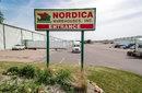Nordica Exterior With Company Sign & Trucks